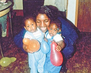 Carol Thomas puts the squeeze on twins Michelle and Michael Pete, all of Youngstown. Othella May of Youngstown sent this photo.