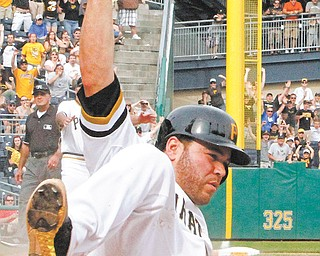 Pittsburgh Pirates' Russell Martin scores the game winning run on an 11th-inning single by the Pirates' Travis Snider off Cincinnati Reds relief pitcher Alfredo Simon to end the game in Pittsburgh on Sunday.