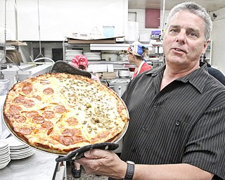Jack Walter, Elmton owner, shows a pizza at his Struthers eatery.