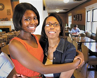 Warren G. Harding High School graduate Taylor Stephenson will attend Youngstown State University this fall on a full-ride scholarship, including room and board. Her mother, Billie Bradley, getting a hug inside of Warren's Mocha House, agrees she could not have afforded to send her daughter to college without the Academic Achievers program.