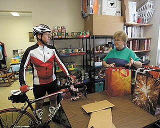 Don Cherry, a bicycling enthusiast and member of Grace United Methodist Church in Warren, talks to Shirley Frazier, the church's food-pantry coordinator, about his upcoming 68-mile bike ride that is a fundraiser for the pantry.