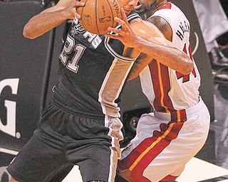 The Spurs' Tim Duncan (21) drives against the Heat's Udonis Haslem during the first quarter of Game 1 of the NBA Finals on Thursday at American Airlines Arena in Miami. Duncan scored 20 points for San Antonio, which won 92-88.