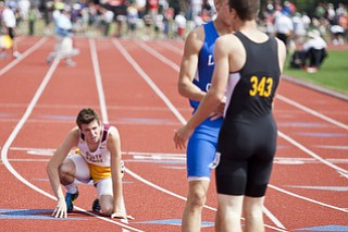 Andrew O'Leary stumbles to his knees after competing in the 400m dash at the state track and field finals at Jesse Owens Memorial Stadium, Columbus, OH, Saturday, July 8, 2013.