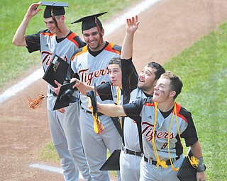 Springfield's five senior players, from left, Chris Bishard, Dom Gentsy, JoJo Carabello, Cody Pitzo and Eoghan Bees toss their graduation caps into the air after receiving their diplomas near home plate at Huntington Park in Columbus before the start of Sunday's Division IV state baseball final against Newark Catholic.