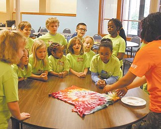 Kristie Gearhart, right, assistant director at the art camp, gets the attention of participants as she shows the result of the tie-dye T-shirt project. Children will wear the shirts during the week.