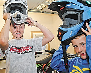 Katherine Kali, 12, left, and her brother, Andrew Kali, 7, of Hubbard put on their motocross helmets. The siblings have competed in motocross events on the local, regional and national levels.