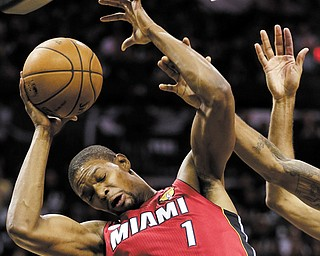Miami's Chris Bosh (1) grimaces as he tries to find some space under the basket during the first half of Tuesday's NBA Finals game in San Antonio, Texas.