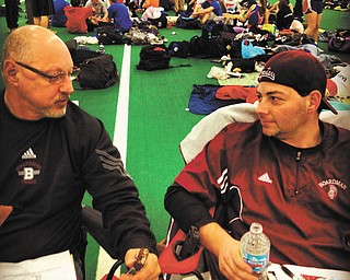 Pictured are two generations of Spartan coaches: John R. Phillips, head boys track and cross-country coach, is discussing strategy at an indoor meet in January at Kent State University with his father and assistant coach, John F. Phillips.