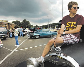 Anthony Marsilio, 16, a South Range High School junior, sits on the hood of his 1929 Ford during the Ninth Annual Father's Day Car Show at South Range High School. Marsilio was showing the car with his father, Hank, who taught him how to drive vintage vehicles.