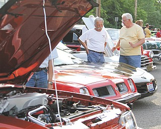 Joe Carbon of Poland, left, talks about his 2002 Corvette with Mike Yajich during Cruisin' the River, which is sponsored by the Lowellville Business Association. The event takes place from 6 to 9 p.m. Mondays, or 5 to 8 p.m. Mondays on and after Labor Day.