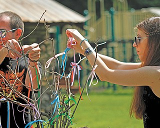 Jason Berg and Lee Sokol of the Silver Grove Society tie ribbons to the ceremonial tree to symbolize things they need during a midsummer ritual at Girard-Liberty Memorial Park. The society is an eclectic pagan community group.