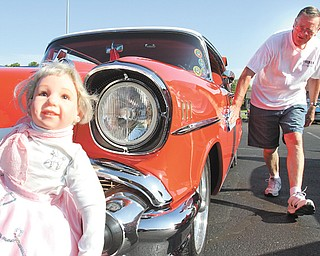"Jerry Apger of Lordstown shines his 1957 Chevrolet while ""Barbie,"" a doll that rides in the back seat of his classic car, sits on the front bumper during the Senior Center Car Cruise in Austintown."