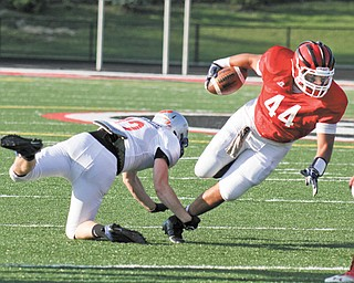 Mahoning's David Stewart (44) of Struthers is tripped up by Trumbull's Brandon Harb (12) of Hubbard during the first half of the 29th Jack Arvin Football Classic on Thursday at Girard's Arrowhead Stadium. Mahoning defeated Trumbull, 34-26.