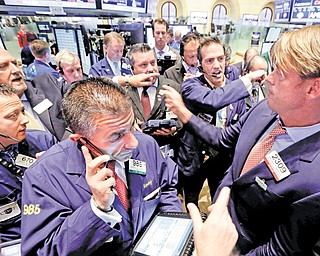 Traders gather at the post of specialist Patrick Murphy, right, on the floor of the New York Stock Exchange