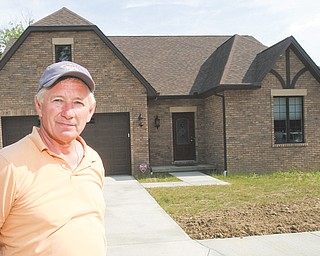 Ken Zuzik, who has been building homes in the Mahoning Valley since 1987, stands near one of the completed units in the Abbey Road Villas development in Canfield.