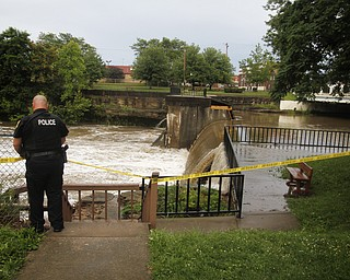 MADELYN P. HASTINGS I THE VINDICATOR  Newton Falls Police Officer Mark Brown taped off a section of the dam near Veteran's Park in Newton Falls over the west branch of the Mahoning River after a storm caused major flooding on July 10, 2013.