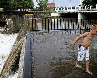 MADELYN P. HASTINGS I THE VINDICATOR  Caiden Miller, 6, of Newton Falls plays in the overflow of the river near the dam by Veteran's Park in Newton Falls over the west branch of the Mahoning River after a storm on July 10, 2013.
