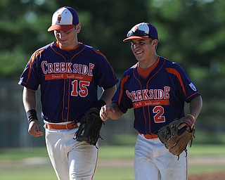 Creekside infielder #2 Steve Sada and teammate #15 Zac Miller both smile while walking of the field after a acrobatic double play by Sada.