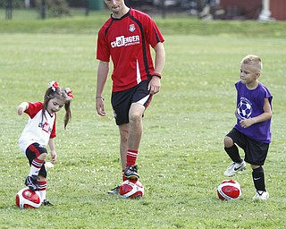 ROBERT K. YOSAY  | THE VINDICATOR  Grace Gershkowitz 4 of Canfield and Abram Davidson 5 of Austintown -  get linstuctions from  John Evans  British soccer camp   Wick Recreation Area of MillCreek Park week-long soccer camp focuses on building skills to play the game along with sportsmanship
