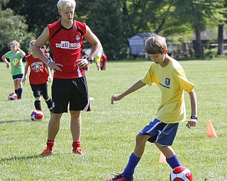 ROBERT K. YOSAY  | THE VINDICATOR  Simon Slater watches as Alec DeBaldo 12 of Austintown   move the ball down the field  British soccer camp   Wick Recreation Area of MillCreek Park week-long soccer camp focuses on building skills to play the game along with sportsmanship