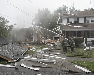ROBERT K. YOSAY  | THE VINDICATOR  firefighters extinguish the house that exploded..  The house at 535 Cohasset Drive was vacant but the house next door at 539 Cohasset is damaged. In addition, at least four homes across the street from the blast had windows that were broken by the force of the explosion.