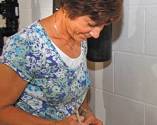 Kathy Murphy of Liberty fills out a water-meter card in her Red Oak Drive basement. The city of Girard is working to transfer its 5,600 water customers from analog, manual-read meters to new remote-read meters — but Murphy, who gets her water from the city, is opposed to the conversion, citing perceived health risks
