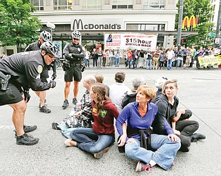 In this photo taken Thursday, a Seattle police officer leans in to explain the arrest procedure to a group of eight protesters blocking a downtown intersection in Seattle. Seattle police said they made several arrests at the demonstration protesting what marchers say are low wages and improper treatment for fast-food workers.