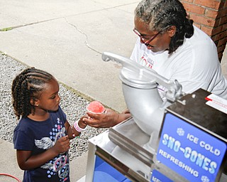 MADELYN P. HASTINGS | THE VINDICATOR..Anita Davis of Youngstown gives 5-year-old Fara Winlock of Youngstown a snowcone at the Youngstown National Night Out at Wick Park on August 6, 2013. This is part of National Night Out program, dedicated to the development and promotion of various crime-prevention programs including neighborhood watch groups, law enforcement agencies, state and regional crime prevention associations, businesses, civic groups, and individuals, devoted to safer communities.... - -30-..
