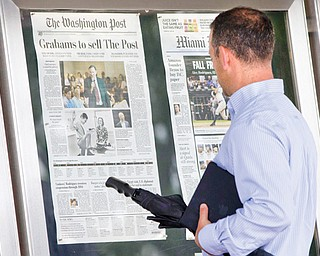 A visitor views the front page of The Washington Post displayed outside the Newseum in Washington on Tuesday, a day after it was announced that Amazon.com founder Jeff Bezos bought the Washington Post for $250 million. Bezos is determined to face the challenge of reversing the newspaper's financial slide.