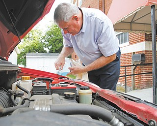 Pastor Ron Maurer of First Christian Church, 140 E. Broadway, Girard, pours windshield wiper fluid into a car just as he will be doing during Inasmuch Day from 10 a.m. to 1 p.m. Saturday. The pastor and a couple of other men from the church will check fluids in cars as part of their day of community service.