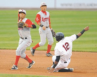 Lowell second basemen Deiner Lopez, left, throws to first base after forcing out Scrappers base runner Claudio Bautista (12) to start a fourth-inning double play Wednesday night.