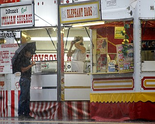 MADELYN P. HASTINGS | THE VINDICATOR  (L-R) Jim Dick of Warren and Roberta Holler of Rootstown working for DiRusso's Italian Sausage try to stay out of the rain that delayed the Warren Italian Festival on Thursday, August 8. The festival runs through Sunday.