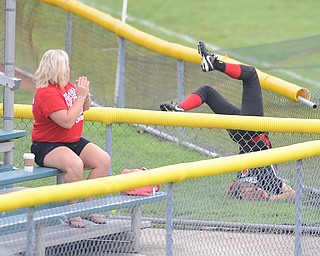Canfield left fielder #1 Bridget Sweeney tumbles over the short left field wall after attempting to catch a ball in foul territory during Thursday morning game against Michigan.