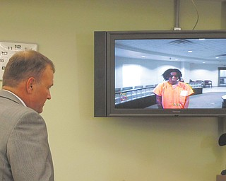 Atty. Mark Hanni stands before a video monitor in Warren Municipal Court on Thursday with his client, Lakeisha Bell,19, of Williamsburg Street Northwest in Warren. Bell is charged in last weekend's death of her friend, McKayla Hopkins, 18, at Bell's birthday party in Perkins Park.