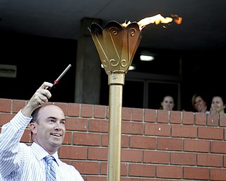 MADELYN P. HASTINGS | THE VINDICATOR..John McNally lights the torch during the Community Cup opening ceremonies at the Central YMCA in downtown Youngstown on Friday, August 9, 2013.... - -30-..