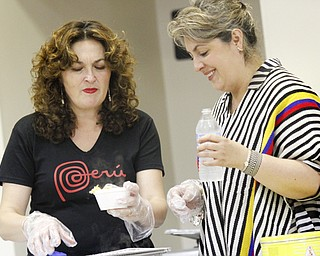 MADELYN P. HASTINGS | THE VINDICATOR..(L-R) Ana Bobby of Peru and Maria Lombana of Columbia serve food at the 2nd Annual International Latino Food Fest at the OCCHA Social Hall in Youngstown on Friday, August 9, 2013. ... - -30-..