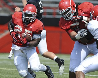 Youngstown State running back #25 Torrian Pace runs the football behind the black of offensive linemen #71 Kyle Bryant during a scrimmage on August 10, 2013.
