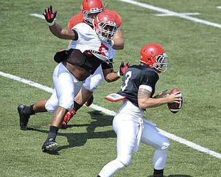 Youngstown State defensive linemen #5 Vince Coleman applies pressure to quarterback #3 Dante Nania after beating offensive linemen #61 Justin Spencer off the ball during a scrimmage on August 10, 2013.