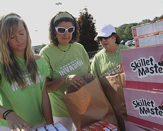 Audrey Dearing (15) of New Middletown, Reba Soldressen of Struthers, and Cathleen Smail of Campbell help pack bags full of groceries during the Goodness Invasion at the Covlli Centre on Saturday Morning.  Dustin Livesay  |  The Vindicator  8/10/13  Covelli Centre.