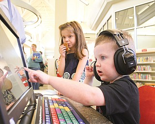 Beckett Liller, 2, and his sister, Harper Liller, 5, examine a computer during Tuesday's dedication of the new $2 million Tri-Lakes Library, 13820 Mahoning Ave., North Jackson. They are the grandchildren of Anne Liller, the library system's manager of urban branches and community outreach. The dedication ceremony was followed by the Outback Ray live animal show.