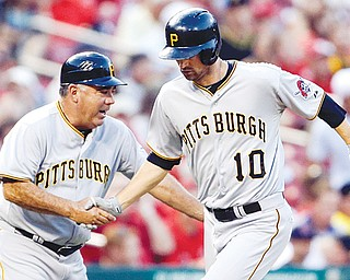 Pittsburgh Pirates' Jordy Mercer, right, is congratulated by third base coach Nick Leyva after hitting a solo home run during the second inning of a game against the St. Louis Cardinals on Tuesday in St. Louis. The game was not completed in time for this edition.