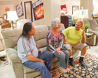 From left, Steve Sanchez, Jackie Calvert and Andy Canady sit on a sofa at the going-out-of-business sale at Bolotin Furniture in Hermitage. The store will be closing after 107 years in business.