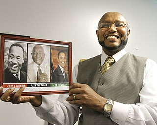 """The Rev. Kenneth Simon, pastor of New Bethel Baptist Church in Youngstown, holds a plaque displayed in his office featuring photos of MLK, Simon's father, the Rev. Lonnie Simon and President Barack Obama with the words, """"I am the dream."""""""
