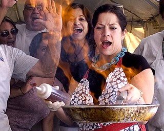 """Kelli Cardinal/The Vindicator Chryse (ok) Ellinos, center, is surrounded by volunteers Saturday while making Saganaki or """"flaming cheese"""" during a traditional Greek Festival at St. John's Greek Orthodox Church on Glenwood Avenue in Boardman."""