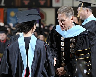 Youngstown State president Randy Dunn shakes the hand of a student after she received her masters degree during the summer commencement ceremony Saturday morning at Beeghley Center.