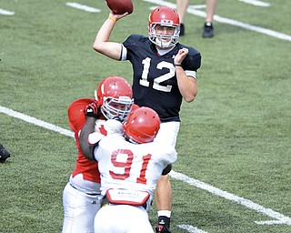 Quarterback Kurt Hess #12 throws a pass from the pocket avoiding the pass rush from #91 Mike Palumbo.