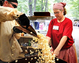 MADELYN P. HASTINGS | THE VINDICATOR  (L-R) Mike Olson and Melissa McKinney make popcorn at the Original Kettle Corn booth at the Shaker Woods Festival in Columbiana on Sunday, August 18, 2013.