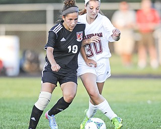 Canfield's Paige Bidinotto, left, and Boardman's Megan O'Neil battle for a ball toward midfield during the first half of Monday's game at Boardman High.