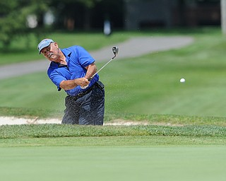Orlando Santiago chips his ball out of the sand trap on the 12th hole Tuesday afternoon at the Trumbull Country club.