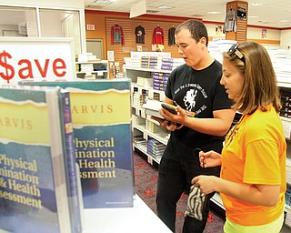 Kevin Casey of New Jersey and Alana Lesnanski of Boardman shop for textbooks Tuesday at the Youngstown State University Bookstore. Classes begin today .